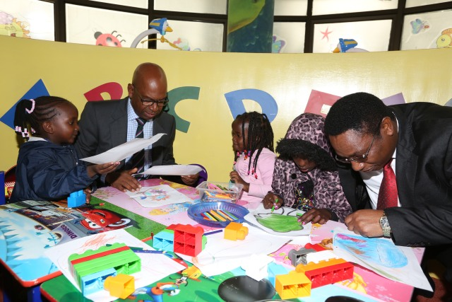 Safaricom CEO Bob Collymore and Dr Kioko helping children at the Safaricom creche with their artwork.